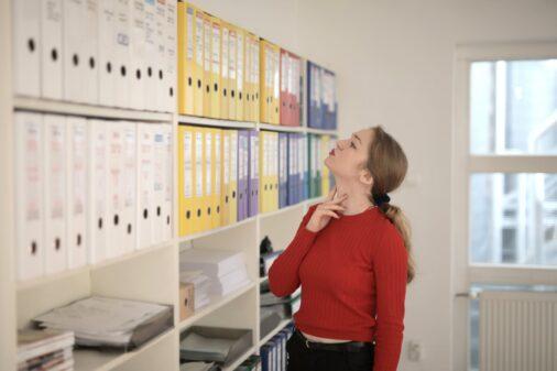 pensive female worker choosing folder with documents in modern office